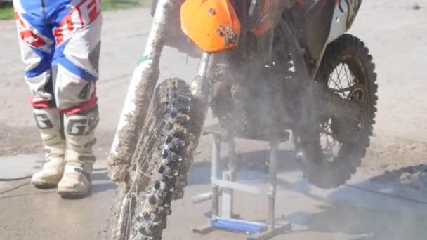 Mann wäscht Rennrad nach dem Wettkampf im Motocross