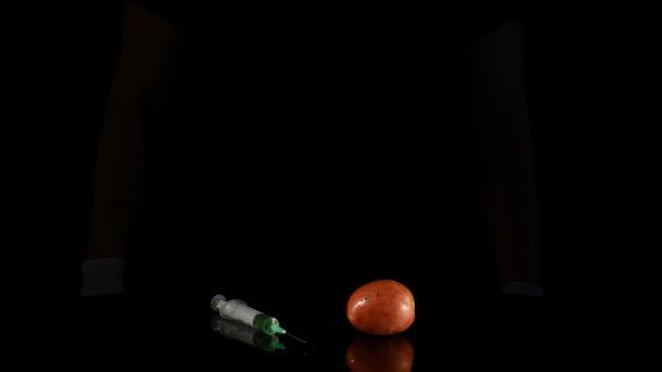 Muž vědec ruce s injekční stříkačkou injekční látky do brambor
