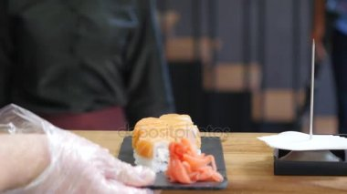 Professional chef cooking, working and preparing Asian food and sushi in restaurant kitchen