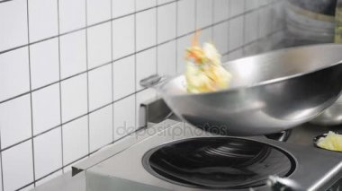 Asian restaurant kitchen, chef cooking food, young man as professional cook working