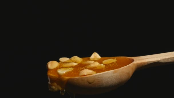Honey and nuts on wooden spoon close up