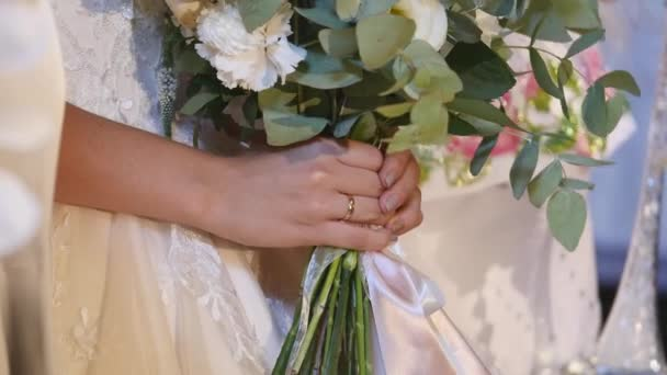 Beautiful bridal bouquet in hands of young bride dressed in white wedding dress. Close up of big bunch of fresh white roses and tulips flowers in female hands. Anonymous bride holding flowers