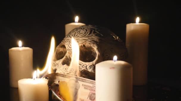 Égő dollárt négy gyertyát, és a koponya felső fekete háttér közelről