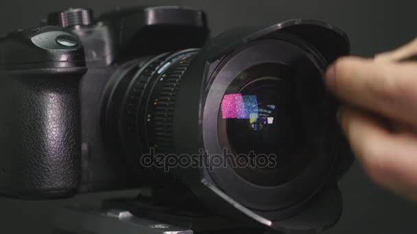 der Fotograf führt die Reinigung des Kameraobjektivs durch