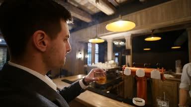 Csinos, fiatal férfi kortyolgatva a bárban. Életmód fogalom