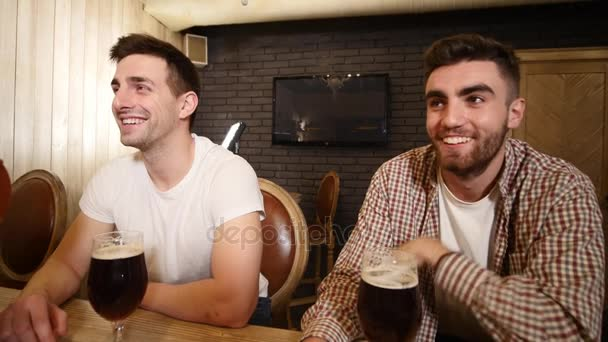 Két kaukázusi meg ünnepli a sikert a sport csapat, a kocsmában. Vonzó fiatal férfiak átölelve a bárban számláló. Boldog sport rajongók csengő a pohár sör