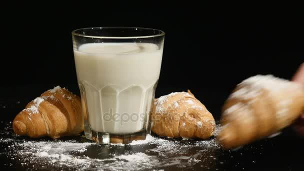 sklenice mléka s croissantem na černém pozadí. ruční vkládání croissant