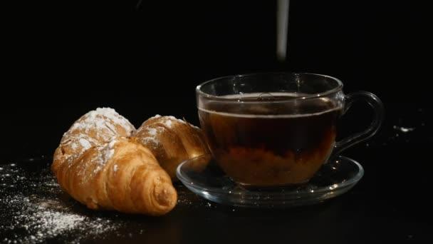Baristy lití mléka v šálek kávy pro aby latte art. káva s mlékem a croissanty na černém pozadí