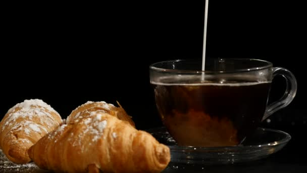 Barista pouring milk in coffee cup for make latte art. coffee with milk and croissants on a black background.