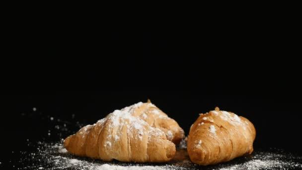 három croissant forgatni a fekete háttér