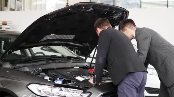 fiatal férfi keresi a motortérben, a márkakereskedés