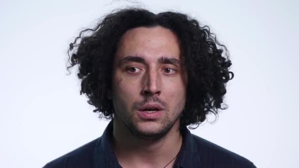 charismatischer bärtiger junger Mann im schwarzen Hemd auf weißem Hintergrund zeigt verschiedene Emotionen