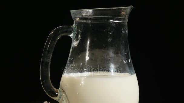 jugful mléka, izolované na černém pozadí