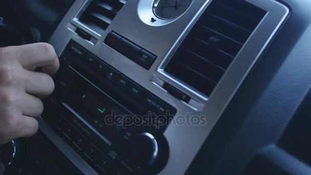 Driver playing car radio, stations shifting