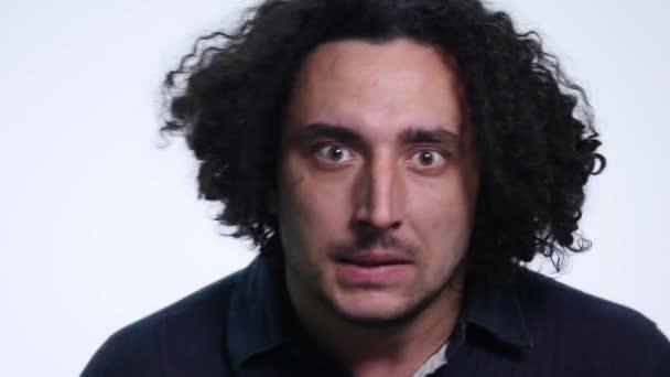 charismatischer bärtiger junger Mann im schwarzen Hemd auf weißem Hintergrund zeigt unterschiedliche Emotionen