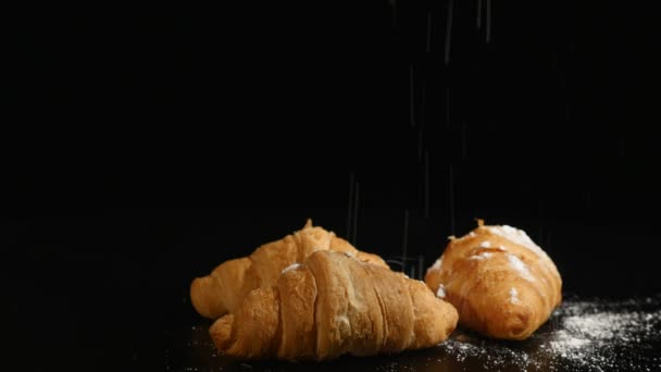 Powdered sugar sprinkling on to a croissant