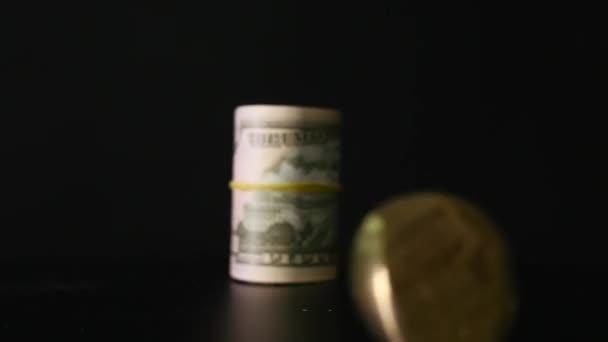 Bitcoin-Münze und die verdrehten Dollarnoten auf schwarzem Hintergrund