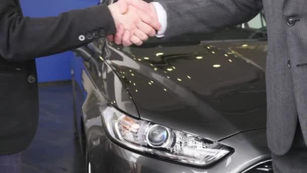 Handshake dvou mužů na nové auto pozadí. Zblízka se mužů pozdrav s handshake. Obchodní partneři handshaking