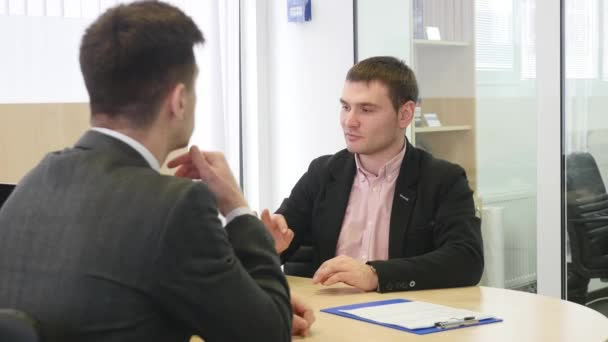 Professional car salesman showing papers to sign to his cutomer. Young handsome man preparing to sign documents while buying a new car safety insurance agreement consumerism vehicle