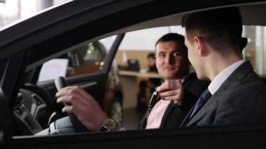 car dealer gives the customer the car keys in car