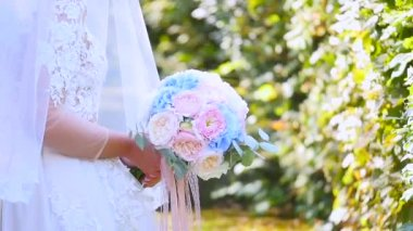 Beautiful bridal bouquet in hands of young bride dressed in white wedding dress