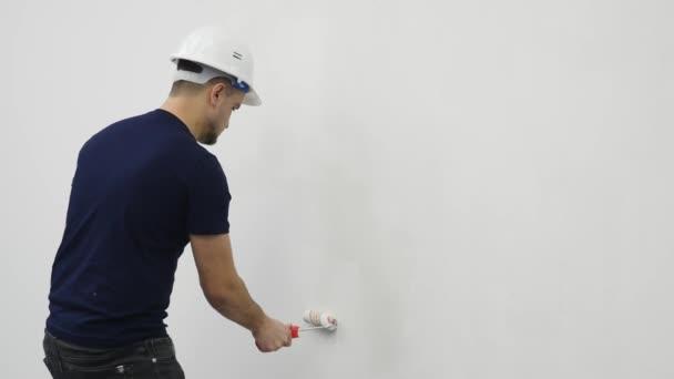 Junger Mann bemalt Wand während Renovierung Haus, 4k