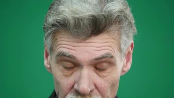 Senior Mann mit Brille isoliert auf grünem Hintergrund