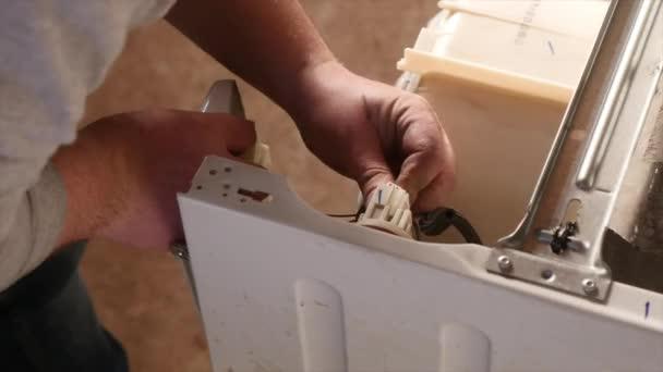 Man trying to fix the washing machine