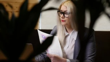 Young Businesswoman working with laptop and documents in cafe