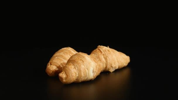 tři croissanty točit na černém pozadí