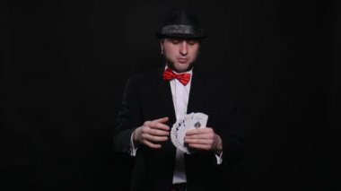 Young magician shows magic playing card trick show concept trick on black background