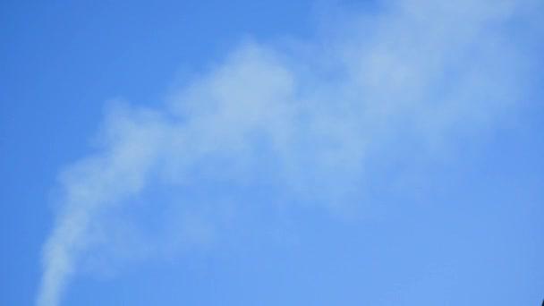 Kouř vychází z komína domu. Potrubí na střeše. Komín. Venkovský dům. Dům s komínem. Kouř na modré obloze. Kouřové komíny a obloha mraky
