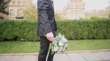 The groom with the bouquet in hand goes
