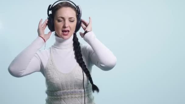 mladá žena, tančí a zpívá na sluchátka na bílém pozadí