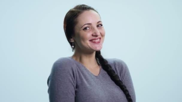 Junge schöne Frau lächelnd, jubelnüber weißen Hintergrund