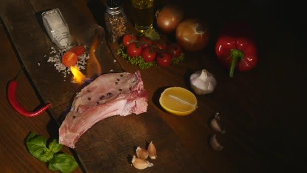Detailní pohled surového kusu masa a chilli a pepř plamen na černém prkénko. gril hovězí steak bbq plameny ohně šťavnatá rajčata koření sůl Příprava exkluzivní výborné jídlo chutné výživy