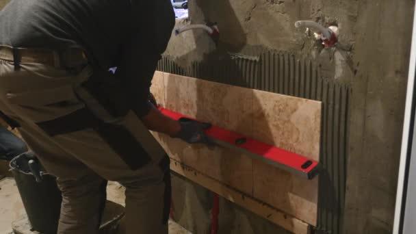 Uvádění keramických dlaždic na stěnu. Keramik je pomalu pokládání keramických dlaždic na zdi koupelny plné speciální lepidla