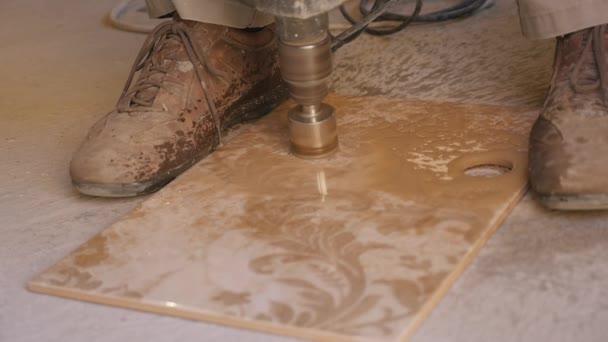 Giovane maestro mette delle mattonelle di ceramica sulla parete in