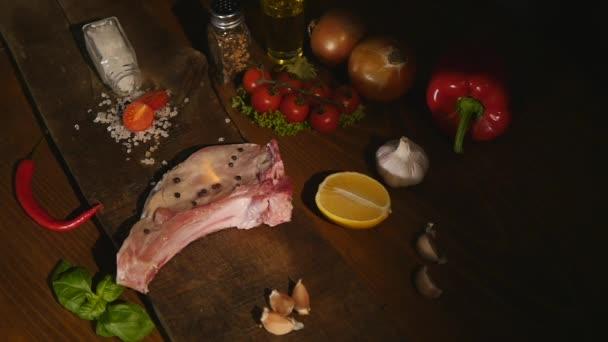 horní pohled surového kusu masa a chilli pepper s plamenem na černém prkénko. gril hovězí steak bbq plameny ohně šťavnatá rajčata koření sůl Příprava exkluzivní výborné jídlo chutné výživy