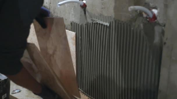 Keramische tegels zetten op de muur. Keramist is langzaam opleggen ...