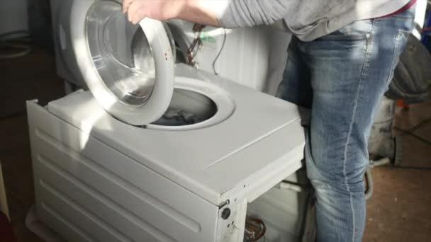 Ein Reparateur demontiert gerade ein Bedienfeld an der Waschmaschine komplett. er muss das ganze Gerät reparieren.