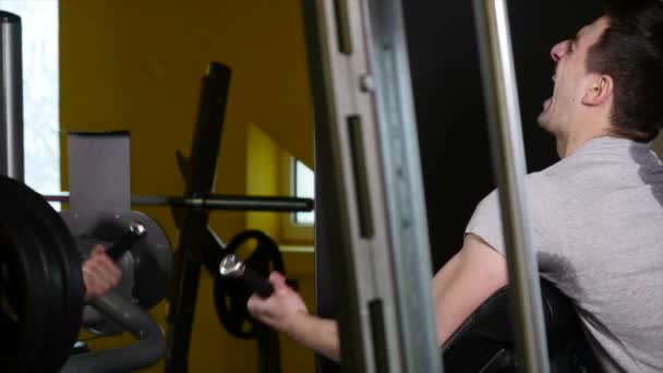 Man with a sports figure doing exercise on simulator in the gym