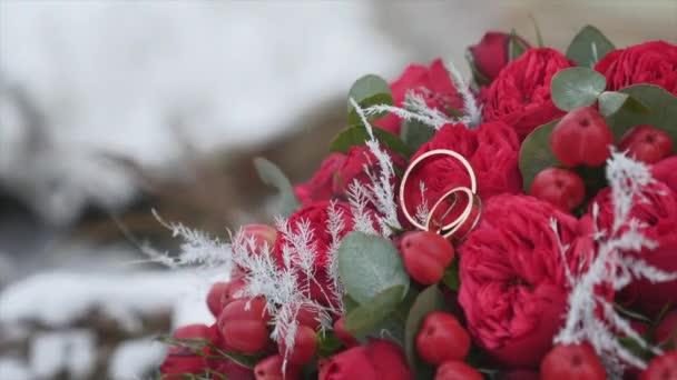 Svatební kytice s snubní prsteny s červenými květy na pozadí sněhu
