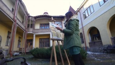 Young artists draw in the city . Artists painting picture on the street. Students paint building of the old European city