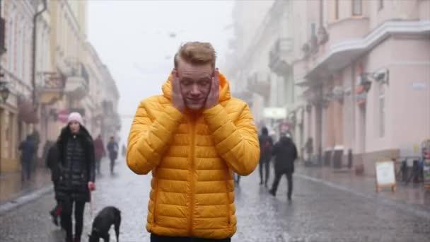 Portrét atraktivní elegantní mladý muž díval do kamery. mladý muž hlavu vzhůru na ulici
