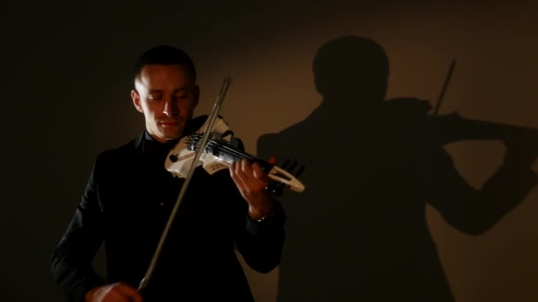 Fiatal férfi hegedül a sötét szobában