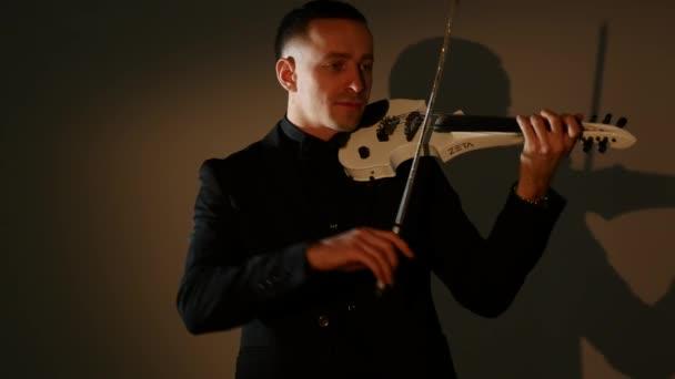Junger Mann spielt Geige im dunklen Raum