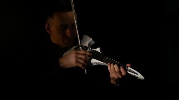 Musician playing a violin on black background