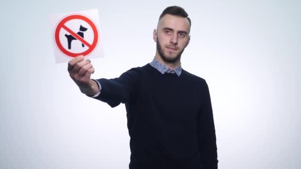 mladý muž, který držel znamení psi nejsou povoleni na bílém pozadí