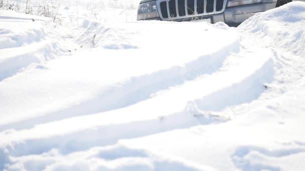SUV s zasněžené kola a zimní pneumatiky jízdu na sněhu, detailní zobrazení